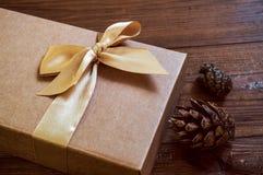 Geschenkbox mit Goldbogen und Kegelfichte auf hölzernem Hintergrund lizenzfreie stockfotografie