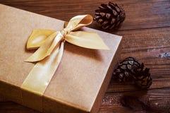 Geschenkbox mit Goldbogen und Kegelfichte auf hölzernem Hintergrund lizenzfreies stockbild