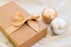 Geschenkbox mit Goldbogen und mit Weihnachtsbällen lizenzfreie stockbilder