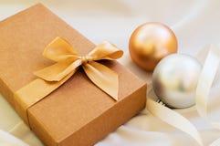 Geschenkbox mit Goldbogen und mit Weihnachtsbällen stockfotografie