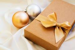Geschenkbox mit Goldbogen und mit Weihnachtsbällen stockfotos
