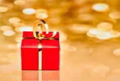 Geschenkbox mit goldenem Hintergrund Lizenzfreies Stockfoto