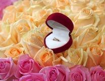 Geschenkbox mit Goldring auf schönem Rosehintergrund Stockfotografie