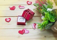 Geschenkbox mit Herzen und Blumen auf hölzerner Tabelle, Valentinsgruß ` s Tageshintergrund Lizenzfreies Stockfoto