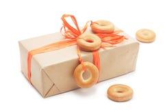Geschenkbox mit orange Band und Bagel Lizenzfreie Stockfotografie