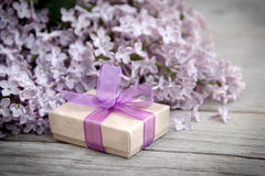 Geschenkbox mit purpurrotem Bogen und Flieder auf Holz Lizenzfreies Stockfoto