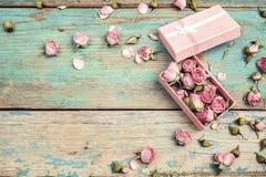 Geschenkbox mit Rosa trocknete rosafarbene Blumen auf altem Türkis hölzernes b Stockbild