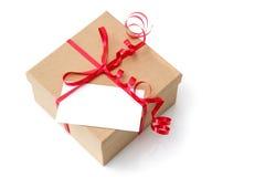 Geschenkbox mit rotem Band und leerer Karte Stockfotografie