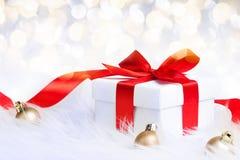 Geschenkbox mit rotem Bandbogen und Weihnachtsball Stockbilder
