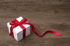 Geschenkbox mit rotem Bogen auf rustikaler Tabelle, Weihnachten oder einer anderen Feier Stockfotos