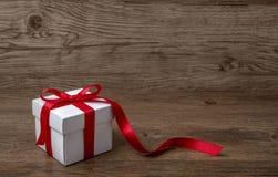 Geschenkbox mit rotem Bogen auf rustikaler Tabelle, Weihnachten oder einer anderen Feier Stockfoto