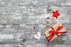 Geschenkbox mit roten Band- und Kiefernkegeln auf grauem Holztisch CH Lizenzfreie Stockbilder