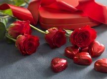 Geschenkbox mit roten Rosen und Schokoladen Roter heart-shaped Schmucksachegeschenkkasten und eine rote Spule auf einem Zeichen Stockfoto