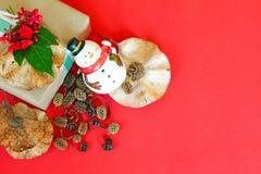 Geschenkbox mit roter Blume, Schneemann, Kiefernkegel und trocknen Blätter auf rotem Hintergrund Lizenzfreie Stockbilder