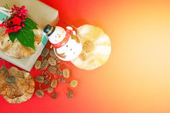 Geschenkbox mit roter Blume, Schneemann, Kiefernkegel und trocknen Blätter auf rotem Hintergrund Stockbild