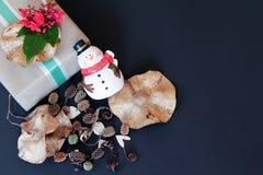 Geschenkbox mit roter Blume, Schneemann, Kiefernkegel und trocknen Blätter auf schwarzem Hintergrund Lizenzfreie Stockfotografie