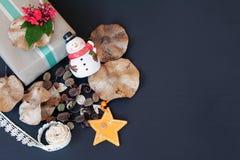 Geschenkbox mit roter Blume, Schneemann, Kiefernkegeln, trockenen Blättern, Sterndekoration und Band auf schwarzem Hintergrund Lizenzfreie Stockbilder
