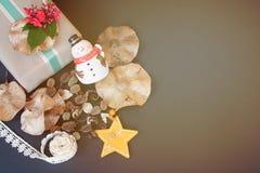 Geschenkbox mit roter Blume, Schneemann, Kiefernkegeln, trockenen Blättern, Sterndekoration und Band auf schwarzem Hintergrund Lizenzfreie Stockfotografie