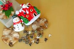 Geschenkbox mit roter Blume, Schneemann, Weihnachtsmann-Haus, Kiefernkegel, trocknen Blätter und Sterndekoration auf goldenem Hin Stockfotos