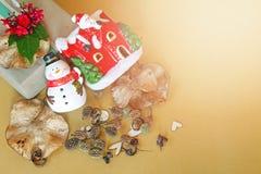 Geschenkbox mit roter Blume, Schneemann, Weihnachtsmann-Haus, Kiefernkegel, trocknen Blätter und Sterndekoration auf goldenem Hin Stockfotografie