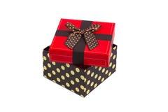 Geschenkbox mit roter Kappe und dem Band, lokalisiert auf weißem Hintergrund Stockfotografie