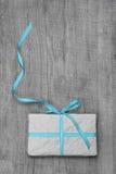 Geschenkbox mit Türkis streifte Band auf einem hölzernen Hintergrund Lizenzfreies Stockfoto
