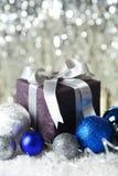 Geschenkbox mit Weihnachtsball auf Schnee, Abschluss oben Lizenzfreies Stockbild