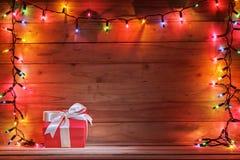 Geschenkbox mit Weihnachtslicht und hölzernem Hintergrund Stockfotografie