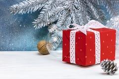 Geschenkbox-, Nuss- und Kiefernkegel auf hölzerner weißer Tabelle gegen blaues b Lizenzfreie Stockfotos