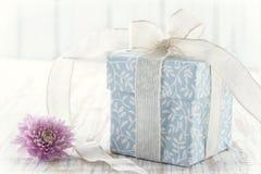 Geschenkbox oben gebunden mit weißem Band und rosa Blume Stockbilder