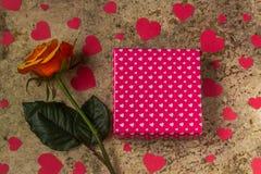 Geschenkbox, rosafarbene Blume und Herzen auf einem hölzernen Hintergrund Lizenzfreie Stockfotografie