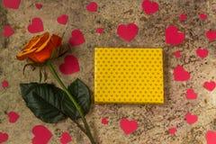Geschenkbox, rosafarbene Blume und Herzen auf einem hölzernen Hintergrund Stockfoto