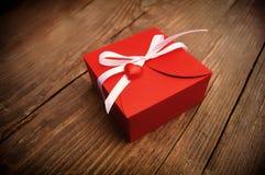 Geschenkbox rote Farbe mit einem weißen Bogen und ein Herz auf einem hölzernen b lizenzfreie stockfotografie