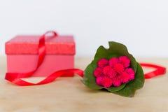 Geschenkbox und Blume verziert durch Band auf Holztisch Stockbilder