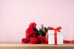 Geschenkbox und bonquet von roten Rosen Stockbild