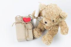 Geschenkbox und Buchstaberolle setzten sich neben einem Teddybären stockbild