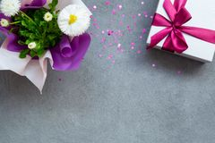 Geschenkbox- und Gänseblümchenblumen auf grauer Steintabelle, Blumenkonzept mit Kopienraum stockbilder