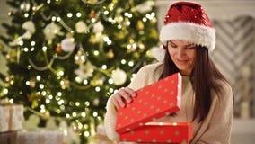 Geschenkbox und lächelnde Frau in Santa Hat über Weihnachtsbaum-Hintergrund Hübscher Brunette mit dem langen dunklen Haar und San stock footage