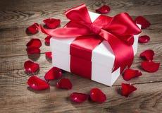 Geschenkbox und rosafarbene Blumenblätter auf den alten hölzernen Brettern stockfotografie