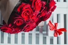 Geschenkbox und rote Rosen Geschenk am Valentinstag für Frau Stockfotografie