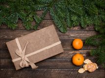 Geschenkbox und Tangerinen mit Tannenzweigen auf rustikalem hölzernem backg Stockfoto
