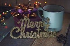 Geschenkbox und Tasse Kaffee, Goldaufschrift auf dem Tisch Stockbild