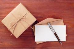Geschenkbox und Umschlag mit Blatt des leeren Papiers und Stift auf Holztisch Stockfoto