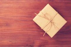 Geschenkbox verpackte in das braune Papier, das durch Schnur auf altem Holztisch mit Raum für Text gebunden wurde Stockfotografie