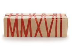 Geschenkbox vom Kraftpapier mit dem roten Band, das Text MMXVII bildet Stockfoto