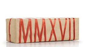 Geschenkbox vom Kraftpapier mit dem roten Band, das Text MMXVII bildet Lizenzfreie Stockbilder