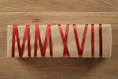 Geschenkbox vom Kraftpapier mit dem roten Band, das Text MMXVII bildet Lizenzfreie Stockfotografie