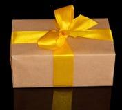 Geschenkbox vom Kraftpapier mit einem gelben Bogen stockbilder