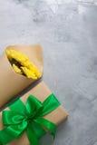 Geschenkboxblumenstrauß-Gelbchrysanthemen auf grauem konkretem backgrou Stockfotos
