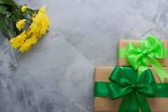 Geschenkboxblumenstrauß-Gelbchrysanthemen auf grauem konkretem backgrou Stockfoto